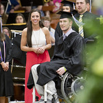 "<b>Chris Norton walks across the stage to collect his deploma.</b><br/> Chris Norton graduates with the class of 2015 and walks across the stage to recieve his deploma with the assistance of his girlfriend and a standing ovation from the crowd. Photo by Aaron Lurth.<a href=""http://farm6.static.flickr.com/5450/18044371802_09e20ff773_o.jpg"" title=""High res"">∝</a>"