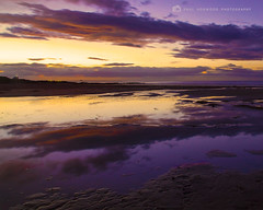 Dusk over Bamburgh Beach (Paul Hogwood Photography) Tags: uk light sunset sea england sky sun reflection beach water grass yellow set clouds reflections lights coast sand rocks dusk dunes north northumberland pools setting bamburgh sets