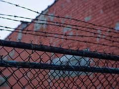 It keeps us from them... (L.M. Brown) Tags: bricks barbed wire color lm brown red focus