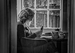 the girl in the cafe window (Daz Smith) Tags: dazsmith canon6d bw blackwhite blackandwhite bath city streetphotography people candid canon portrait citylife thecity urban streets uk monochrome blancoynegro mono girl female woman eating sandwich cafe window light reading book sitting