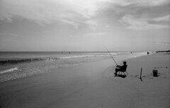 Resplendent (F. Neil S.) Tags: bwfp blancetnoir ilford delta 100 xtol selfdev negative film beach sand curl wave horizon paddleboards fisherman seated silhouette breaking surf relax bucket rod stroll walkers clouds latedaysun latesummer boguebanks downeast northcarolina crystal coast crystalcoast holiday