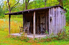 Rocking chair waiting. (GeryLee) Tags: building architecture serene outdoor cabin door texture porch frontporch rocker rockingchair posts grass surrounded abandoned rural wooden old