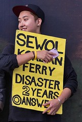 Sewol Korean Ferry Disaster, now more than  two years ago (chrisjohnbeckett) Tags: sewol korea ferry disaster protest demonstration politics world yellow black trafalgarsquare london londonist timeout street urban people chrisbeckett canonef135mmf2lusm portrait candid answer guilt blame yoobyungeun humanitarian smile mobile phone cellphone global photojournalism southkorea