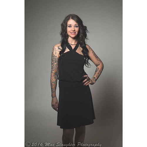 Jessika in a simple black dress showing the ink on her arms.