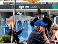 Dont Look we are Being Capatured (Jocey K) Tags: newzealand christchurch buildings city signs architecture people street newregentst cafes chairs tables clouds shops mural streetart painting artwork hats wizard