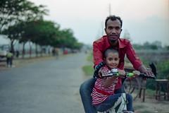 Happiness in Their Eyes... (Sheikh Shahriar Ahmed) Tags: street red film bicycle shirt pose happy 50mm evening kid nikon child fujifilm dhaka nikkor f18 bangladesh banasree nikonf6 af50mmf18d fujicolorc200 dhakadivision aftabnagar epsonv330 sheikhshahriarahmed