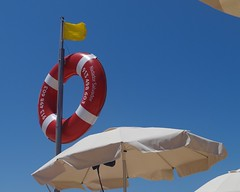 Parasol with Lifebuoy (Snowdrop500) Tags: ocean sea summer sky holiday beach portugal sand europe algarve sunbathing albufeira parasols umberellas