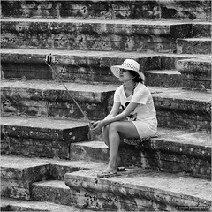 Sticks and stones... (John Riper) Tags: johnriper street photography straatfotografie square bw black white zwartwit mono monochrome candid john riper canon 6d 24105 l cyprus κύπροσ amphitheatre selfie stick lady woman hat mickey mouse shirt smart phone