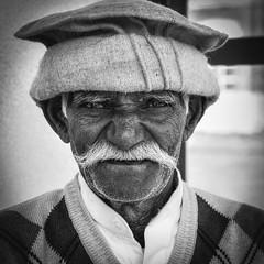 Mr Grey (eyecandyclick) Tags: man asian hat busstop moustache shirt portrait justoneclcik bristles wrinkles wornface oldman manchester infrontofthelens concentration ilovephotography
