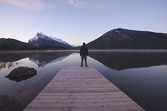 A man standing on a pier in Vermillion Lake in Banff Park, Canada (vix227) Tags: park lake snow canada man mountains reflection standing rockies pier spring alone bc outdoor hiking lakes canadian national alberta lone environment banff hiker vermillion