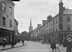 Hill Street, Newry, County Down (National Library of Ireland on The Commons) Tags: eason easonson easoncollection easonphotographiccollection glassnegative 20thcentury nationallibraryofireland hillstreet newry northernireland ireland ulster posing spire church bonnets bicycle shops countydown williamritchiesonsltd wrs ohaganstreet fosterltd ajmacmillan mcmillan jeweller johnquinn