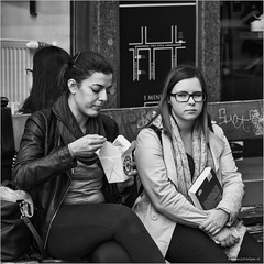 Reading does not satisfy one's hunger (John Riper) Tags: johnriper street photography straatfotografie square vierkant bw black white zwartwit mono monochrome hungary budapest candid john riper fujifilm fuji xt1 18135 girls young women sitting bench contemplating snack box eating glasses map padthai wokbar wok2go zwvk