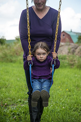 A little girl on a swing with her mom pushing her (MarleneFord) Tags: portrait girl face childhood concentration intense toddler child play serious expression mother swing innocence push intensity concentrate individuality seriousness
