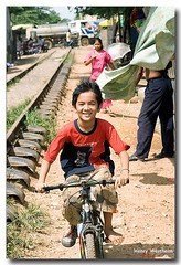KHMhw302 (Henry Westheim Photography) Tags: poverty travel boy people bike bicycle train asian happy asia cambodia child poor young tracks destination southeast phnom penh