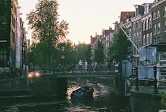 (Tori Taylor) Tags: canon t50 film photography colour fujifilm 35mm sunset amsterdam netherlands holland bridge canal people city europe road trip windows vernacular architecture trees boat boats golden gold hour street