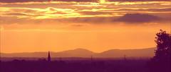 Setting sun, Sutton Weaver (Rupert Thomson) Tags: suttonweaver orange settingsun sun clouds spire churchspire silhouette tree hills