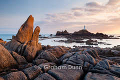 Evening light, Corbire Lighthouse - Jersey (Graham Dunn Photography) Tags: landscape spring unitedkingdom dramatic jersey jagged geography englishchannel causeway channelisland lacorbire orangepinksky corbierelighthouse dusksunset outdoorsoutside wornweathered seaseascape britishbritain geologygeological rockrocky april2013 coastcoastalcoastline viewvistascenesceneryscenic completedin1874 southwestjersey