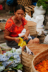 flower seller (Sam Scholes) Tags: travel flowers vacation bali orange woman flower digital shopping indonesia nikon colorful forsale market candid baskets vendor shopkeeper d300 sukawati gianyar sukawatimarket