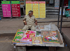 Poster Seller (cowyeow) Tags: market marketplace streetmarket business trade pune india indian street asia asian travel maharashtra city candid people composition man dude poster religion religious faith table