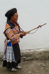 A woman plays an music instrument for goodbye ... (Rita Willaert) Tags: china tribal guizhou miao minority musicinstrument southwestchina lusheng minderheden bijie foursealmiao villageniuchangba