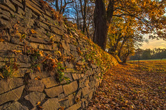 the wall (bocero1977) Tags: stone autumn landscape nature germany mood outdoor fall light trees blue bricks fence shadow gold sundown sky foliage colors green wall clouds park field