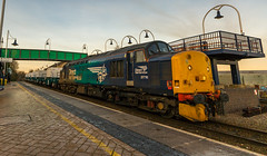 DRS Class 37/7 no 37716 passes through Mansfield Woodhouse Station on 30-11-2016 with 6 new Nuclear Flask wagons bound for Crewe (kevaruka) Tags: shirebrook mansfieldwoodhousestation mansfield nottinghamshire derbyshire whdavis class37 37716 trains train transport railway colour colours blue yellow green red bridge drs directrailservices networkrail britishrail historic classic heritage history englishelectric england autumn 2016 november canon canoneos5dmk3 canon5dmk3 canonef1635f28mk2 did uwa ultrawideangle 5d3 5diii 5d 5dmk3 outdoor telephototrains kevinfrost photography eos