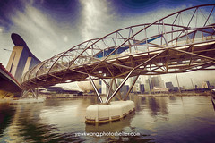 The Helix Bridge 01 (DP) (yewkwangphoto) Tags: sea seascape water horizontal museum architecture skyscraper reflections shopping landscape singapore cityscape bluesky tourist nightscenery placeofinterest commercialbuildings buildingstructure photocategory marinabaysand yewkwang artsciencemuseum thehelixbridge photographybyyewkwang