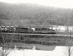 Two B&O GP40's haul autos and general freight westbound along the Youghiogheny River near Connellsville, Pennsylvania, with the Western Maryland's mainline across the river in the background. 1973 (Ivan S. Abrams) Tags: blackandwhite newcastle pittsburgh butler bo ge prr ble conrail alco milw emd ple 2102 chessiesystem westmorelandcounty 4070 bessemerandlakeerie steamtours pittsburghandlakeerie ivansabrams eidenau steamlocomtives ustrainsfromthe1960sand1970s
