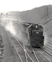 "Brakeshoe smoke surrounds an eastbound freight as it comes down ""The Slide"" at Bennington Curve, about a mile east of Tunnel Hill, Pennsylvania, 1976 (Ivan S. Abrams) Tags: blackandwhite newcastle pittsburgh butler bo ge prr ble conrail alco milw emd ple 2102 chessiesystem westmorelandcounty 4070 bessemerandlakeerie steamtours pittsburghandlakeerie ivansabrams eidenau steamlocomtives ustrainsfromthe1960sand1970s"
