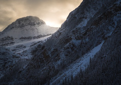 Sombre Glow (Darren Umbsaar) Tags: mountains mountain mount mistaya lake lakeshore cliffs cliff slope avalanche glacier cold winter snow ice sun light glow sunny evening sunset final last golden air misty clouds cloudy blue zoom telephoto banff national park alberta canada rockies rocky canadian