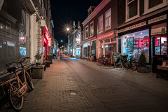 Late Night Tales (McQuaide Photography) Tags: haarlem noordholland northholland netherlands nederland holland dutch europe sony a7rii ilce7rm2 alpha mirrorless 1635mm sonyzeiss zeiss variotessar fullframe mcquaidephotography lightroom adobe photoshop tripod manfrotto light licht night nacht nightphotography stad city urban lowlight architecture outdoor outside illuminated street straat kleinehoutstraat window wideangle wideanglelens groothoek building longexposure blackandwhite oldstreet old oud character traditional authentic streetlight bike bicycle fiets shop winkel shopwindow atmosphere sfeer