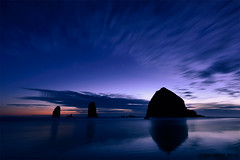 Blue Cannon Beach (Dan Mihai) Tags: ocean longexposure blue sunset orange seascape motion beach night clouds oregon reflections stars landscape coast landscapes twilight seascapes sundown pacific silhouettes vivid haystack cannonbeach haystackrock seastacks