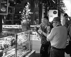 Shoot the Olives (Halcon122) Tags: madrid street camera bw woman man photo spain couple raw photographer market candid streetphotography stranger tourists elderly olives determined cameraman mercadosanmiguel epm2