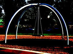 The Swing (Steve Taylor (Photography)) Tags: swing chain blue black brown green red white metal steel rubber newzealand nz southisland canterbury christchurch city cbd grass tree shadow silhouette sunny sunshine margaretmahy margaretmahyplayground playground park