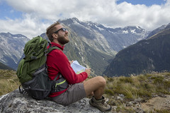 In montagna (boiron.italia) Tags: youngmen men males arrival dirtroad fiordlandnationalpark backpack reaching sitting looking oneperson achievement challenge contemplation gettingawayfromitall journey freedom enjoyment happiness red greencolor blue ontopof direction highup traveldestinations nature outdoors positiveemotion hiking recreationalpursuit beard people milfordtrack southland southislandnewzealand newzealand summer mountainrange mountain landscape sky footpath map sunglasses