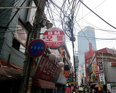 "Seoul Korea tons of dangling wires in crowded cluttered backalley - ""There's Some Electricity in the Air"" (moreska) Tags: travel urban signs english tourism asia mess backalley market lodging sightseeing korea cables wires seoul highrise hanging flea exploration dangling clutter dongdaemun packed crammed hangul motels tangled sidestreet mishmash muddle sensoryoverload citified"
