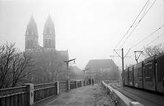Cold, grey and mist (Nekr0n) Tags: street leica city bridge schnee winter people blackandwhite bw mist snow film church monochrome bike 35mm vintage germany deutschland grey blackwhite nikon leute nebel kodak tmax strasse cosina streetphotography kirche tram rangefinder ishootfilm m nostalgia 25 stadt biker streetphoto 100 135 5000 freiburg 35 schwarzweiss baden coolscan m6 manualfocus f25 voigtlnder cv pii leicam6 colorskopar tmx analoge primelens herzjesukirche strase filmisnotdead messsucher imbreisgau voigtlndercolorskopar3525