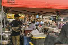 Color of Autumn 2016 In NYC (Street Fair With Lots Of Food Preparation For The Masses On Broad St. In Lower Manhattan) (nrhodesphotos(the_eye_of_the_moment)) Tags: dsc0078072 colorofautumn2016innyc season autumn outdoorevent foodfestival broadstreet cooks chefs patrons outdoor foodpreparation manhattan nyc man women candid people food utensils pots pants tent streetfair shops malls stall room dining reflections shadows streetsigns boxes cartons windows glass panes buildings architecture hats