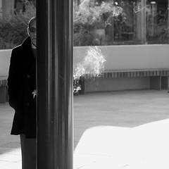 Not shopping (Andrew Malbon) Tags: sigma sigmadp3 dp3 dp3m merrill foveon 50mmf28 50mm fixedlens fixedfocallength street streetphotography smoking man hiding column overcoat windowshopping notshopping reluctant portsmouth strongisland candid blackwhite bw monochrome mono