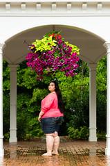 Alyssa (sweeneybrandon) Tags: pink flowers black brick green girl rain shirt hair portraiture hanging archway seniorportrait