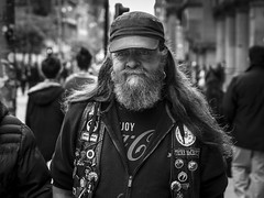 Triker With Attitude (Leanne Boulton) Tags: monochrome people urban street candid portrait portraiture streetphotography candidstreetphotography candidportrait streetportrait eyecontact streetlife man male face facial expression beard cap badge buttons leather biker trike attitude eyes hair tone texture detail depthoffield bokeh natural outdoor light shade shadow city scene human life living humanity society culture canon 7d 50mm black white blackwhite bw mono blackandwhite character glasgow scotland uk