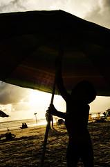 The Parasol (PauloFotografoSantista) Tags: light boy sun luz sol praia beach brasil umbrella garoto sp parasol fim shooting sao tarde guarda entardecer sebastiao juquehy fotografando