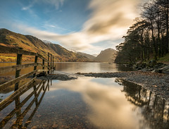 Buttermere reflections (99damo) Tags: lakedistrict water lake cumbria cold winter snow fell buttermere frost long exposure nikon cloud blue gold sky sunrise sun fence shore stone rock