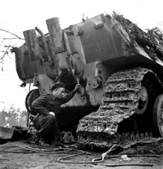 Private W.G. Lourie examines a German Jagdpanther which was put out of commission by the first shot from an Ordnance Quick-Fire 17-pounder gun of the 6th Anti-Tank Regiment, Royal Canadian Artillery, in the Reichswald; Germany - 16 March 1945