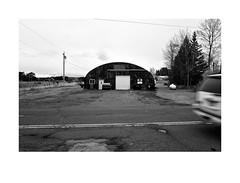 Quonset Hut near Esko, Minnesota (Richard C. Johnson: AKA fishwrapcomix) Tags: leicaq summilux28mm f17 paxamericanus endofempire digital duluth minnesota esko blackandwhite bw monochrome wetzlar decay decline thegreatrecession economicdownturn rural vehicle car countryroad sunsetsinthewest sunrisesintheeast quonsethut autumn leafless wires pole tarmack asphalt