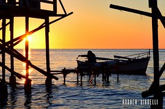Fishing at the sunset (AndreaTigerVianelli) Tags: sunset tramonto sun pesca fishing pescatore mare marine acqua allaperto pescando sea andrea vianelli nikon d5100 orange landscape calma calm