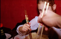 Learning by doing (cotnari73) Tags: zenit122 helios447 fujisuperia200 c41 vivitar2800flash chinesefood sticks learning children child restaurant analog analogue chopsticks