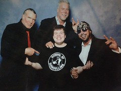 """Michael Brown with the Kliq, sporting his """"School of Overselling"""" shirt"""