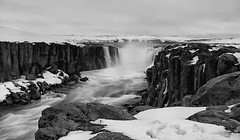 water defying landscape challenges (lunaryuna) Tags: iceland northeasticeland jkulsfjllumriver selfoss waterfall rivercanyon columnarbasalt winterinspring snow ice season spring seasonalbeauty seasonalchange le longexposure water wilderness landscape weathermood lunaryuna blackwhite bw monochrome