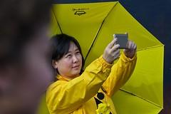Candid portrait, London (chrisjohnbeckett) Tags: yellow selfie umbrella candid portrait london street urban londonist timeout camera mobile phone technology me canonef135mmf2lusm chrisbeckett black smile trafalgarsquare